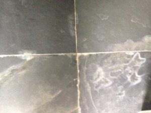 Foto van een natuurstenen oppervlak met kalkaanslag.